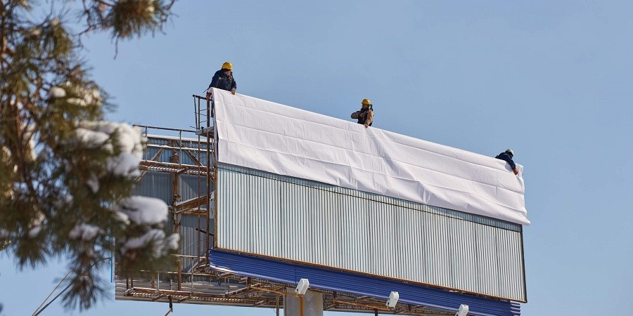 Three workers on top of a billboard, about to unfurl a poster that is due to be posted